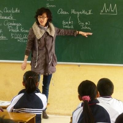 A volunteer explains an exercise to her students on the blackboard during her teaching work experience in Vietnam